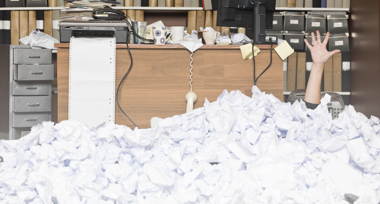 person drowning in a stack of paper