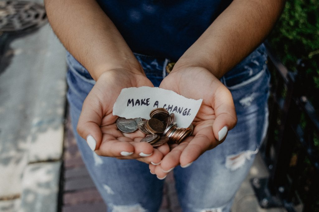 hands open with a pile of change and piece of paper that says make a change